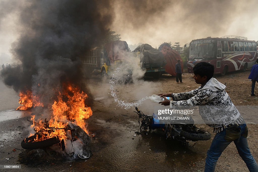 A bystander attempts to extinguish a burning motorcycle set ablaze by Bangladesh Nationalist Party (BNP) supporters during a protest in Narayanganj, on the outskirts of Dhaka, on December 9, 2012. Bangladesh police fired rubber bullets and tear gas at opposition protesters across the country as they tried to block roads and highways to press for their demand for polls under a caretakler government. AFP PHOTO/Munir uz ZAMAN