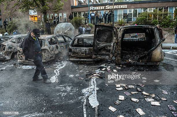 A bystander checks the debris of a burnt out cars in the Stockholm suburb of Rinkeby after youths rioted in several different suburbs around...
