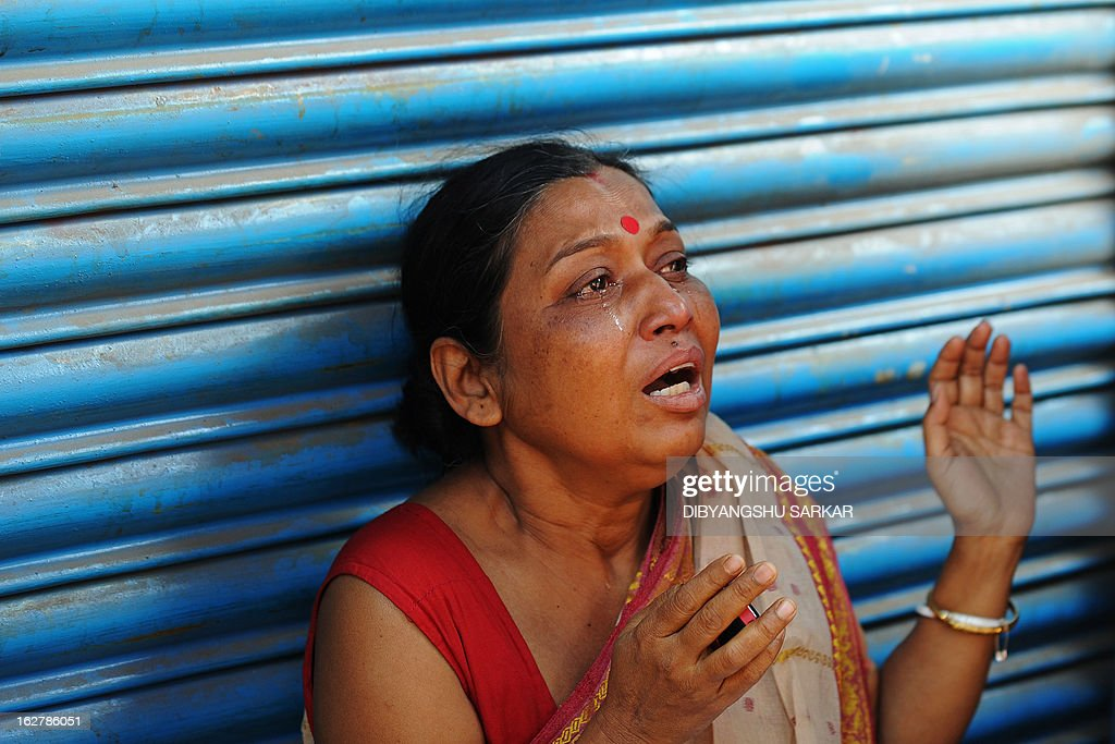 A bystander cries as she watches her office burn during a fire at the Surya Sen market building in Kolkata on February 27, 2013. A fire swept through a six-storey building housing an illegal market in the eastern Indian city of Kolkata, killing 13 people who were unable to escape the inferno, local officials said. AFP PHOTO/Dibyangshu SARKAR