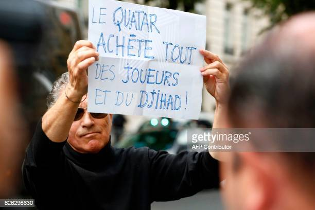 A bystander holds a placard which translates as ' Qatar buys everything some players and some Jihad' as a vehicle understood to be transporting the...