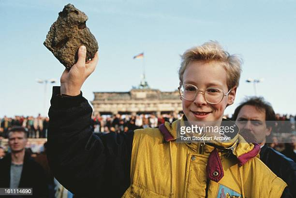 A bystander holds a souvenir chunk of masonry from the Berlin Wall during the Fall of the Berlin Wall 10th November 1989