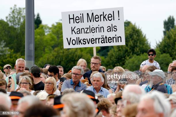 A bystander holds up a sign criticising German Chancellor and head of the German Christian Democrats Angela Merkel during an election rally at the...