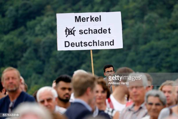 A bystander holds up a sign saying 'Merkel damages Germany' referring to German Chancellor and head of the German Christian Democrats Angela Merkel...