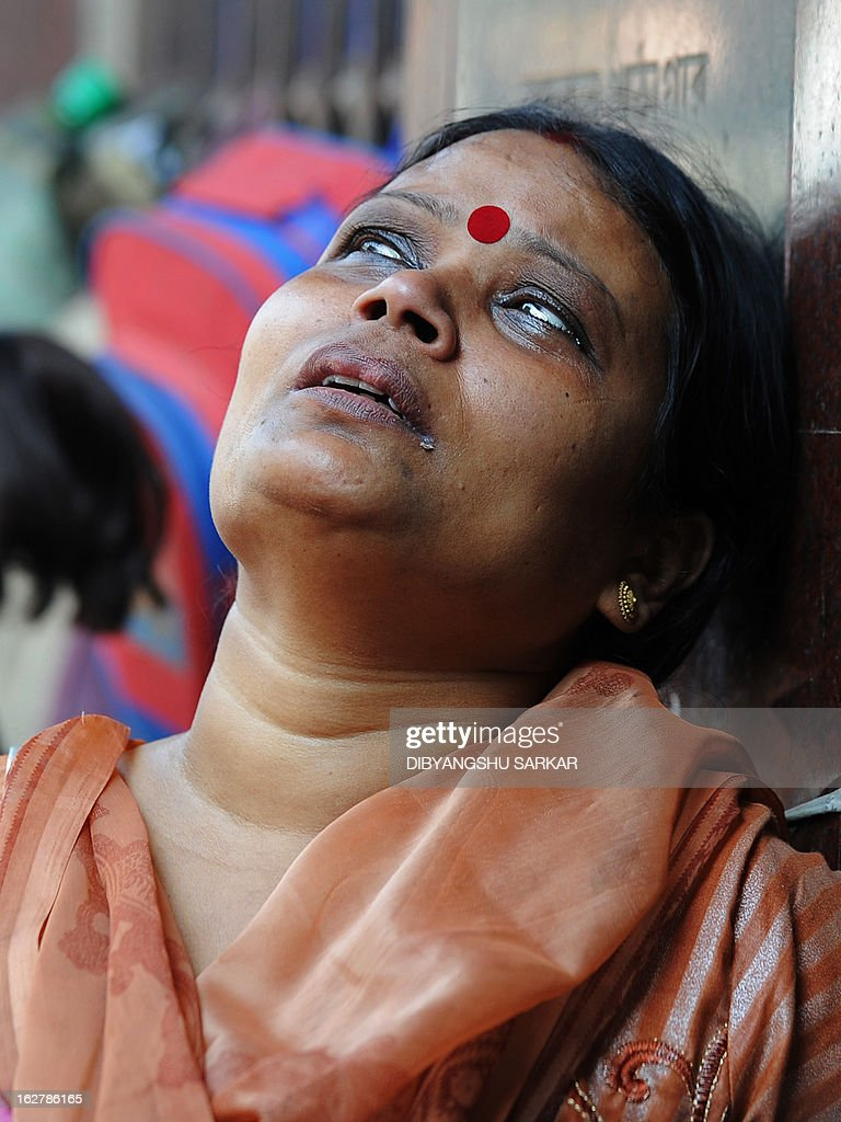 A bystander reacts as she watches her shop burn during a fire at the Surya Sen market building in Kolkata on February 27, 2013. A fire swept through a six-storey building housing an illegal market in the eastern Indian city of Kolkata, killing 13 people who were unable to escape the inferno, local officials said. AFP PHOTO/Dibyangshu SARKAR