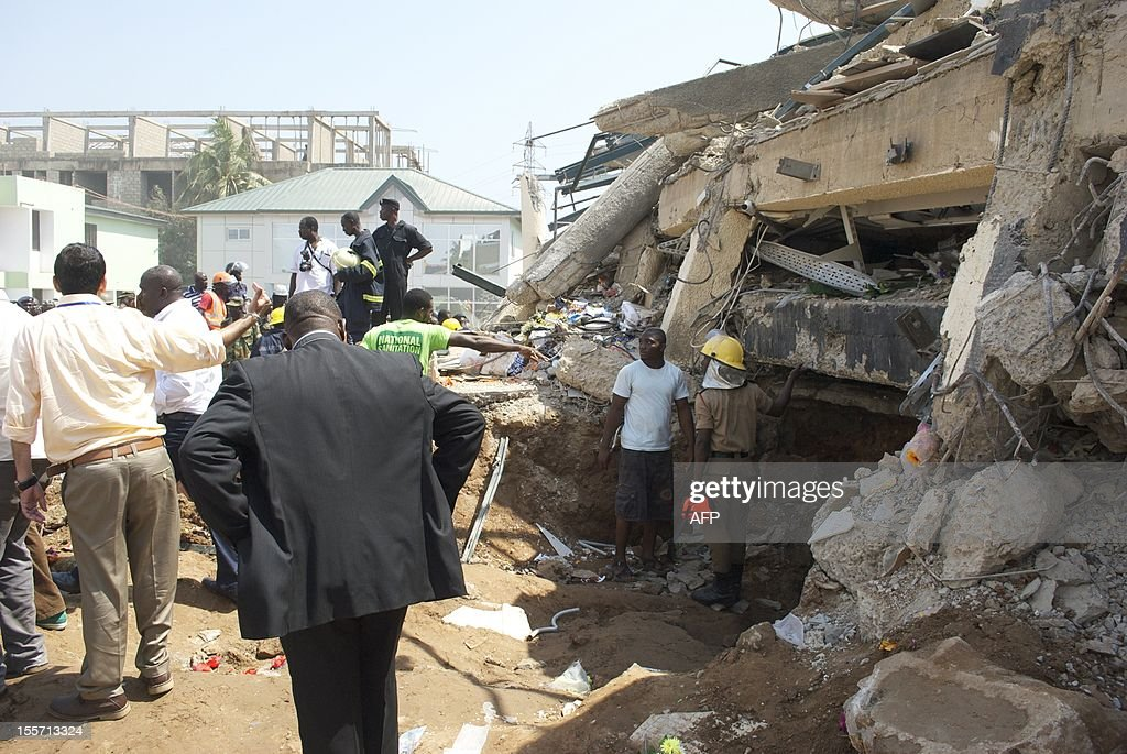 A bystander stands outside a collapsed shopping centre on November 7, 2012 in Accra, Ghana, that killed at least three people and trapped dozens of others. Police said around 50 employees were reported to be in the building before the collapse early on November 7. Rescuers have so far pulled 39 people out alive from the rubble of the shopping centre, police said, after three people were confirmed dead. AFP PHOTO / Christ Estein
