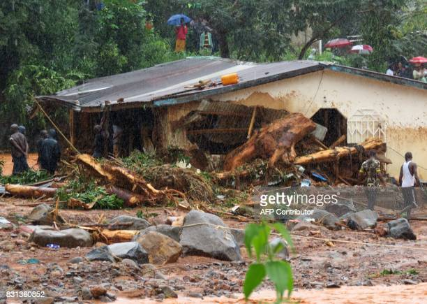 TOPSHOT Bystanders and rescue personnel gather beside a flood damaged building in an area of Freetown on August 14 after landslides struck the...