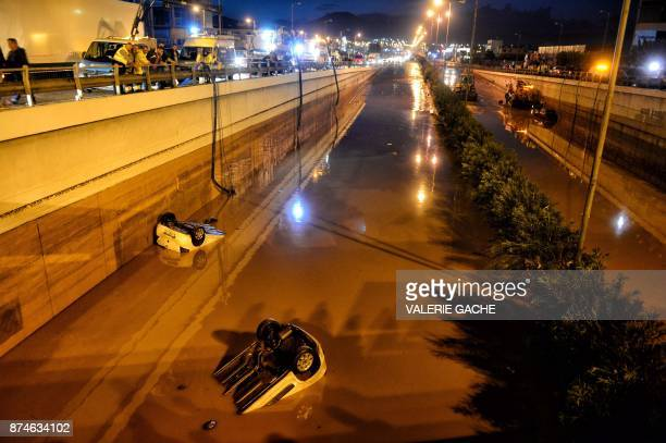 Bystanders and rescue personnel look at vehicles submerged in floodwaters on a highway near Eleusina southwest of Athens on November 15 after heavy...