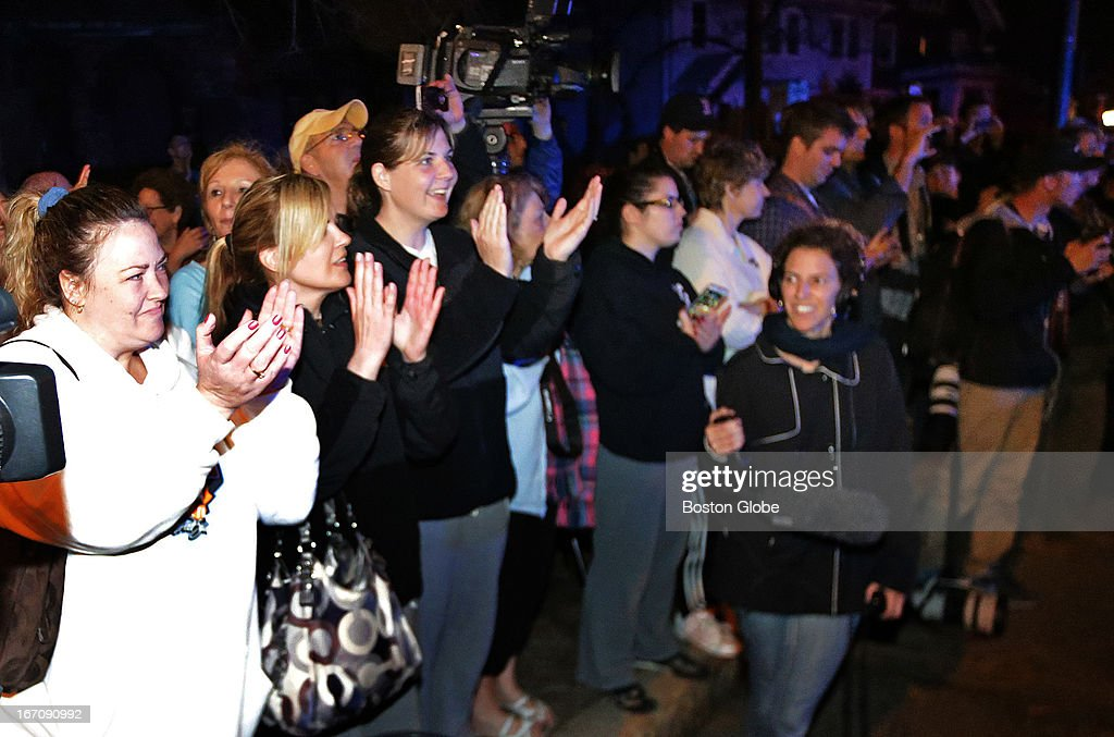 Bystanders cheer at the scene after it was announced the suspect had been captured. After an intense manhunt and two-hour standoff in Watertown, law enforcement took a person into custody believed to be related to the Boston Marathon bombings.