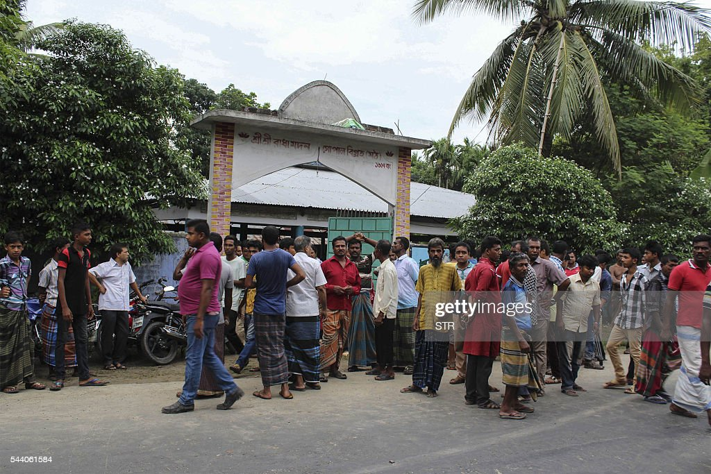 Bystanders gather after Hindu priest Shyamananda Das was hacked to death in Jhenaidah some 211kms north-west of Dhaka on July 1, 2016. A Hindu temple worker was hacked to death in western Bangladesh, police said, the latest in a series of attacks on religious minorities by suspected Islamists. / AFP / STR