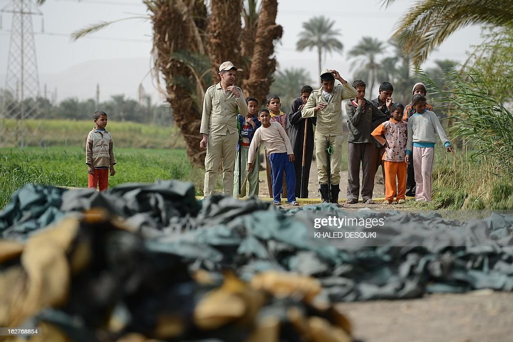 Bystanders gather near the site of a hot air balloon accident in Luxor on February 26, 2013. A hot air balloon exploded and plunged to earth at Egypt's ancient temple city of Luxor during a sunrise flight, killing up to 19 tourists, including Asians and Europeans, sources said.