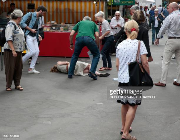 TOPSHOT Bystanders give assistance after Les Republicains party candidate Nathalie KosciuskoMorizet collapsed following an altercation with a man...