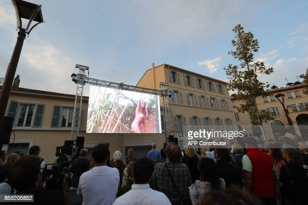 Bystanders look at a big screen showing images of French actress Brigitte Bardot during the inauguration of a statue of her in SaintTropez on...