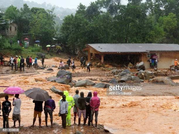 TOPSHOT Bystanders look on as floodwaters rage past a damaged building in an area of Freetown on August 14 after landslides struck the capital of the...