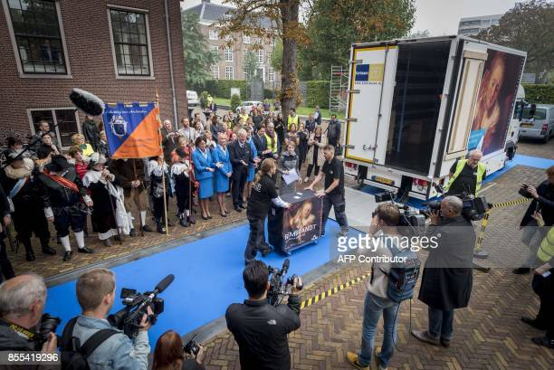 Bystanders look on as workers shift paintings from a truck at The Hermitage Museum in Amsterdam on September 29 where they will form an exhibition of...