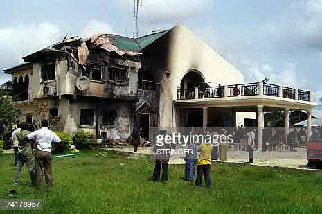 Bystanders looks at the private residence of vicepresident elect Dr Goodluck Jonathan destroyed by an unknown group of Niger Delta militias with...
