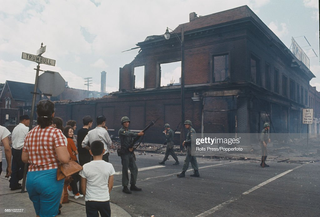 Bystanders observe National Guardsmen, armed with rifles standing guard and patrolling a street corner beside a burnt out brick building on the West Side of Detroit following three days and nights of rioting sparked by a police raid on an unlicensed bar in July 1967.
