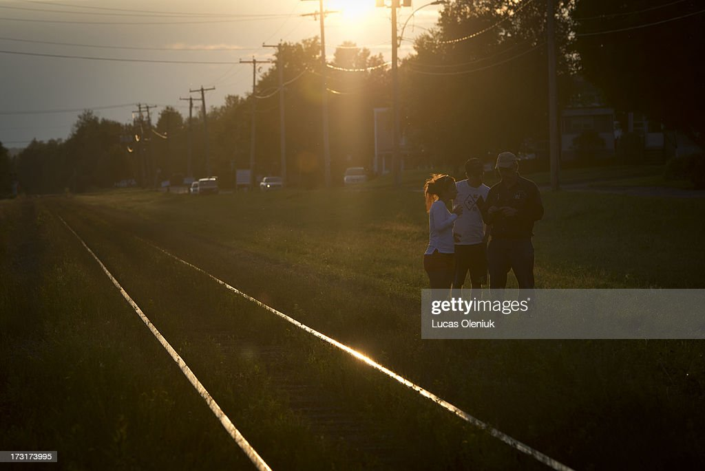 Bystanders reviewed photographs beside the tracks on the perimeter of the crash site as the sun set Monday night in Lac-MÈgantic.