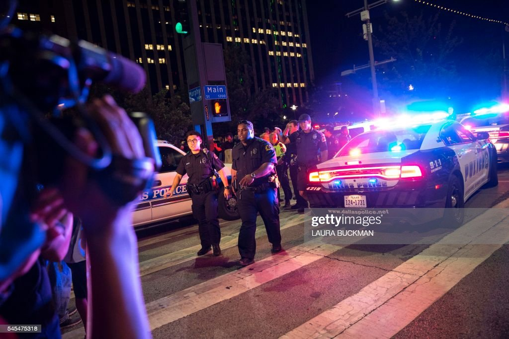 TOPSHOT Bystanders stand near pollice baracades following the sniper shooting in Dallas on July 7 2016 A fourth police officer was killed and two...
