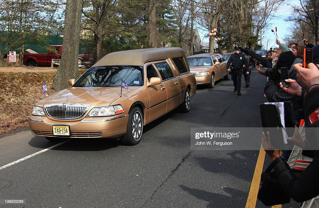 Bystanders throw flowers at the hearse carrying the body of singer Whitney Houston as it arrives for her burial service at the Fairview Cemetery on February 19, 2012 in Westfield, New Jersey. Whitney Houston was found dead in her hotel room at The Beverly Hilton hotel on February 11, 2012.