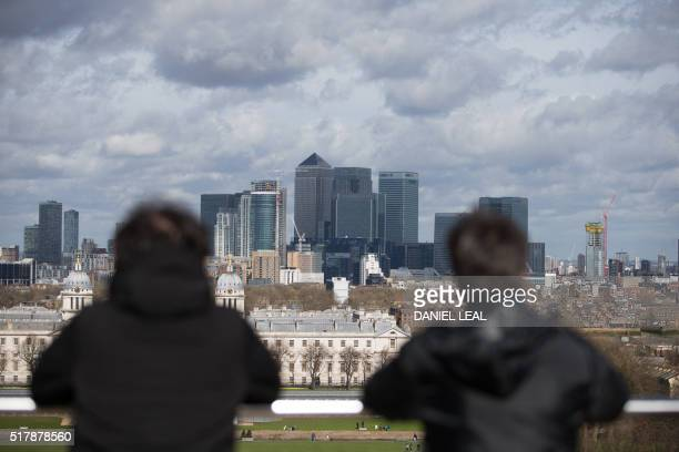 Bystanders visiting the Royal Observatory Greenwich look at the skyline of the London's financial district Canary Wharf in London on March 28 2016 /...