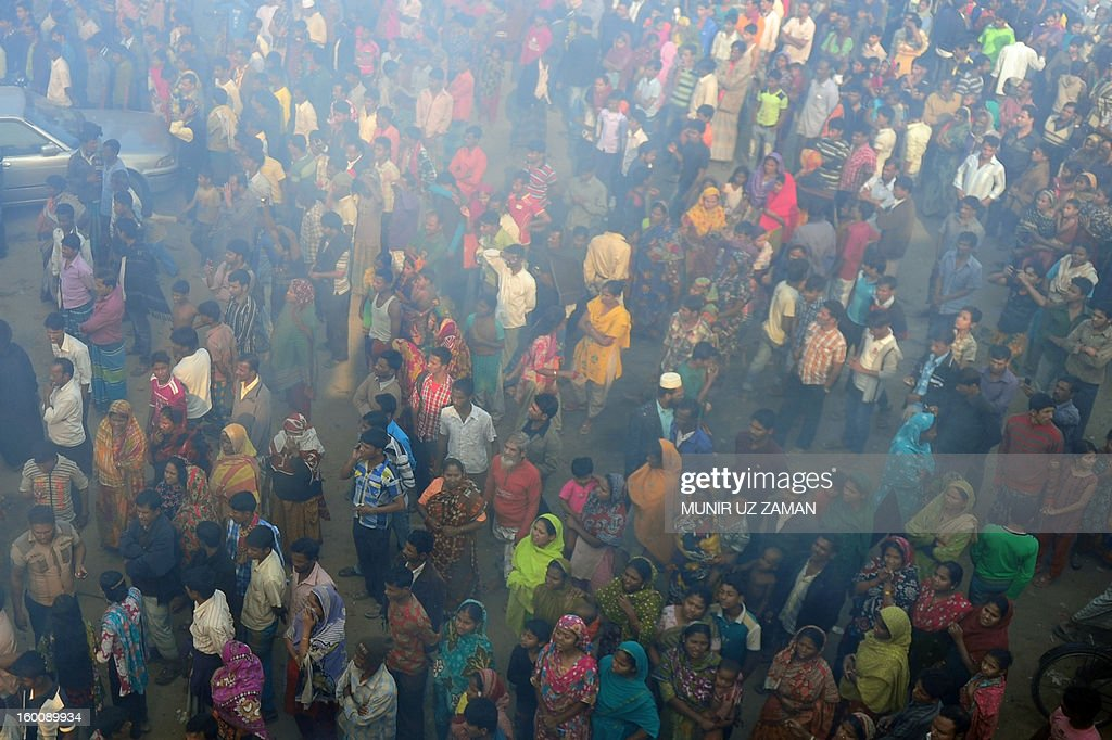 Bystanders watch as Bangladeshi firefighters and volunteers attempt to extinguish a blaze at a garment factory in Dhaka on January 26, 2013. At least six workers at a garment factory in the Bangladeshi capital were killed in a stampede as a fire broke out. AFP PHOTO/Munir uz ZAMAN