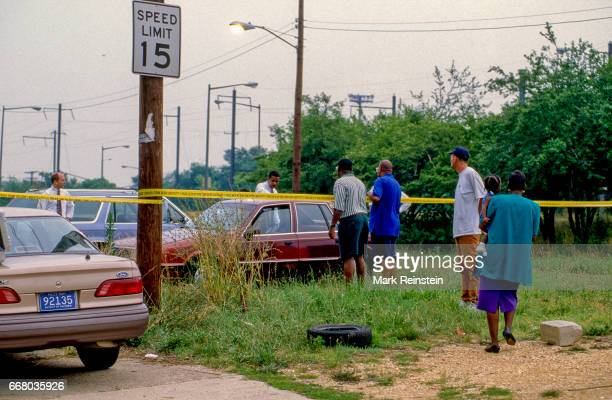 Bystanders watch as DC homicide detectives examine evidence in a car at a murder crime scene Washington DC 1996 The victim's body was found in the...