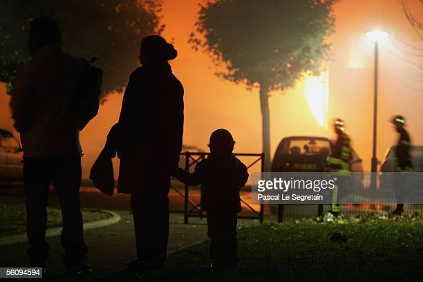 Bystanders watch as firefighters battle a warehouse fire November 4 2005 in Aubervilliers on the outskirts of Paris France Violence was reported...