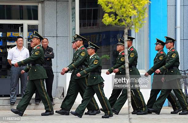Bystanders watch as paramilitary police march on patrol near a vocational school in Xilinhot on May 30 2011 in Inner Mongolia northwest China Tight...