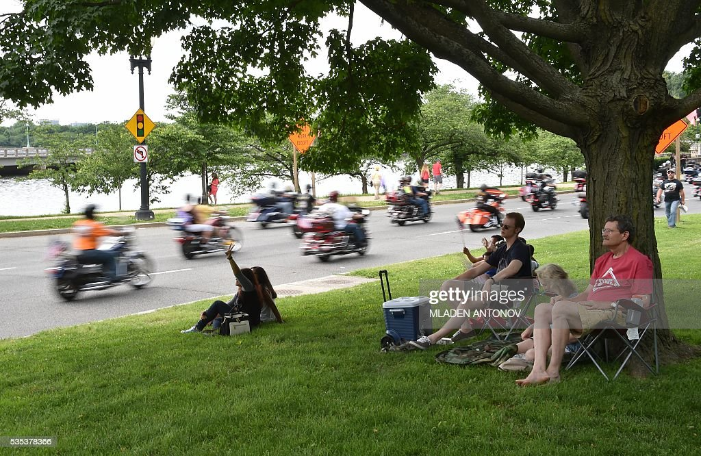 Bystanders watch the annual Rolling Thunder 'Ride for Freedom' parade ahead of Memorial Day in Washington, DC, on May 29, 2016. / AFP / MLADEN