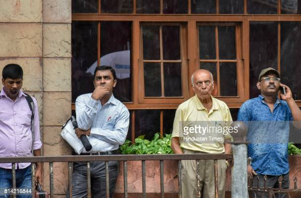 Bystanders watch the digital broadcast on the facade of the Bombay Stock Exchange displaying the benchmark share index SENSEX crossing 32000 points...
