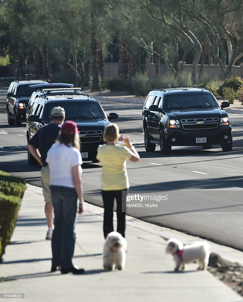 Bystanders watch the motorcade of US President Barack Obama it takes him from the gym back to the resort where he is staying in Rancho Mirage, California on February 14, 2016. / AFP / MANDEL NGAN