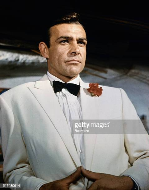 Waistup portrait of Sean Connery as James Bond leaning against a bar and looking out across the room Connery is wearing a white tuxedo and bow tie...