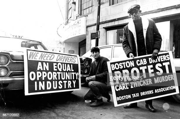 Cab drivers Edward Ferragamo left and TF Jackson attach signs to their cabs as they prepare to participate in a motorcade of about 200 Boston taxi...