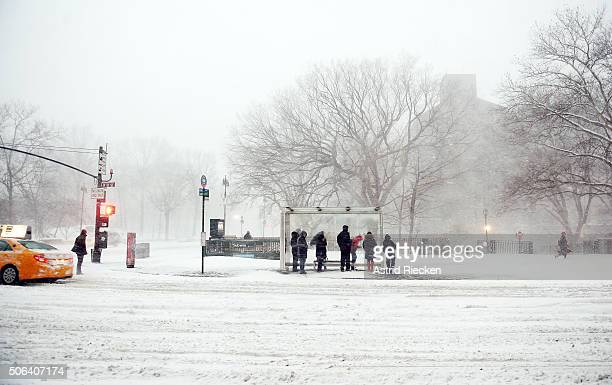 Cab drivers pass by commuters waiting at a bus station on West 81 Street during heavy snow fall and strong wind gusts on January 23 2016 in New York...