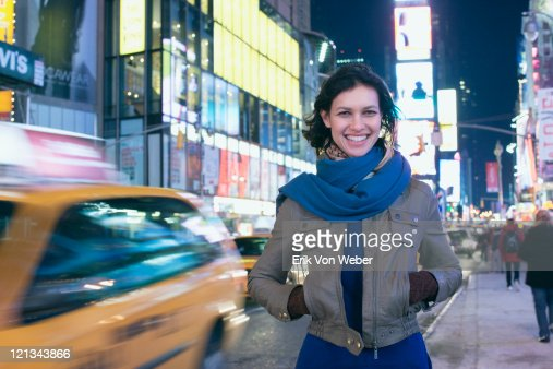 Cab passing woman in Times Square at night : Stock Photo