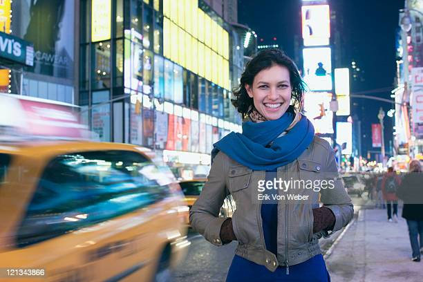 Cab passing woman in Times Square at night