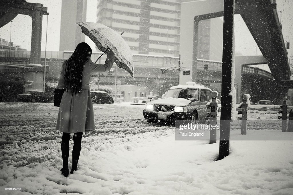 CONTENT] A cab stops for a woman during a rare snow in Tokyo.