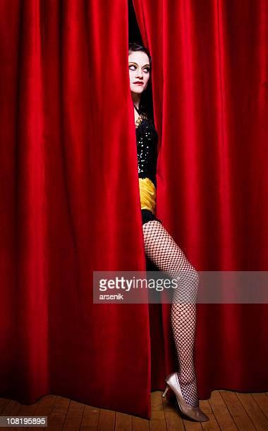 Cabaret Dancer Sticking Leg Through Crack in Curtain