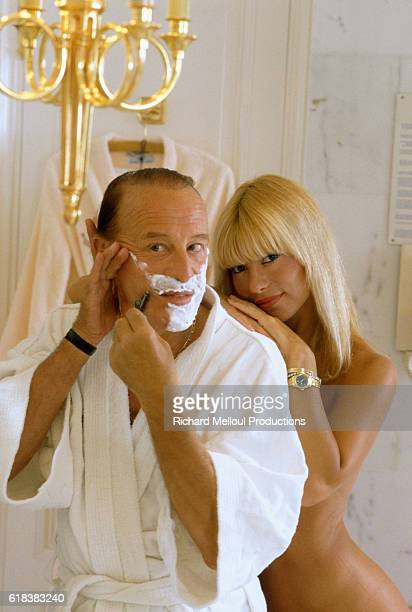Cabaret owner Alain Bernardin shaves while his fiance cabaret dancer Lova Moor stands with him in the nude Bernardin founded the Crazy Horse Saloon a...