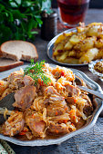Cabbage stew with turkey meat in a metal dish, selective focus