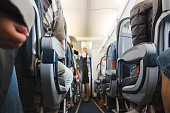 Cabin aisle in airplane with rows of seats and passengers.