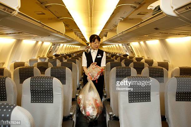 A cabin attendant carries bags of trash as she conducts her cleaning duties in the cabin of a Japan Airlines Co airplane at Haneda Airport in Tokyo...