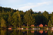 Cabin coastline on Saranac Lake bathed in the morning sunrise. The colored cabins are reflected in the water.