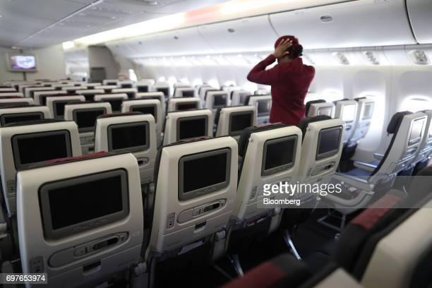 A cabin crew member walks down an aisle onboard a Qatar Airways Ltd Boeing Co 777 passenger aircraft during the 53rd International Paris Air Show at...