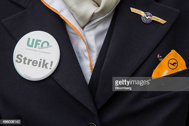 A cabin crew member wears a pin badge with the word strike and the Independent Flight Attendant Organisation cabin crew union logo on her uniform...