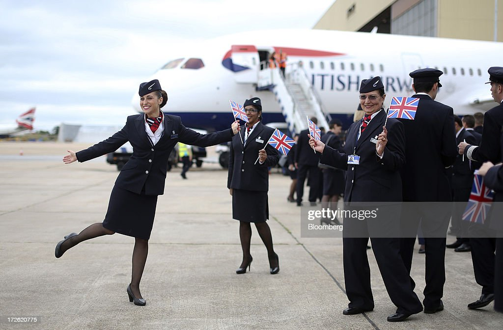 Cabin crew pose for photographs in front of the new Boeing Co 787 Dreamliner aircraft operated by British Airways at Heathrow airport in London UK on...