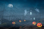 A cabin in a spooky and misty Halloween forest at night with Jack O'Lanterns and ghosts.