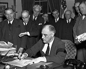 Cabinet members watch with mixed emotions as President Franklin D Roosevelt wearing a black armband signs the United States' declaration of war...