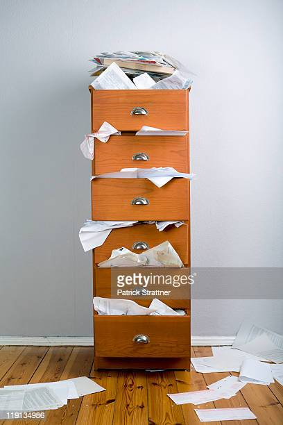 A cabinet stuffed with overflowing papers