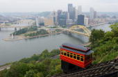 A cable car on the Duquesne Incline a funicular railway climbs a hill overlooking downtown Pittsburgh Pennsylvania on September 22 as the city...